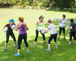 A group of women with fitness trainer in a grassy field at an local park. Sydney, Australia